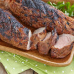 Grilled pork tenderloin served on a wooden board